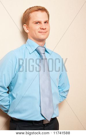 Portrait of a young businessman standing against wall