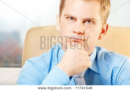 young thoughtful businessman in doubt about something
