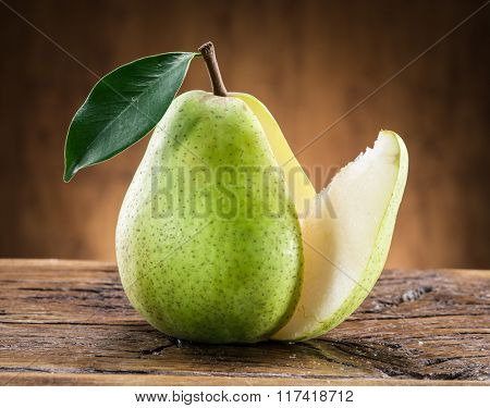 Pear fruit with leaf on wooden background.