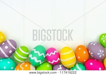 Easter egg border against a white wood background