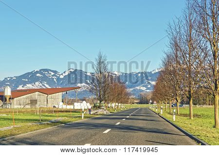 Road View Of Countryside And Snow Covered Swiss Mountains