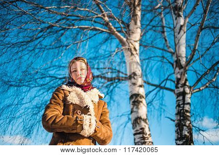 Beautiful blond woman in russian winter suit stay near the birch and thoughtfully looks afar. Girl c