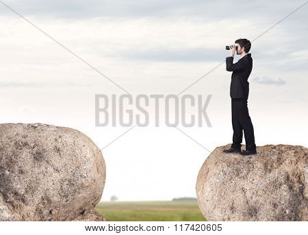 Young businessman standing on edge of rock mountain