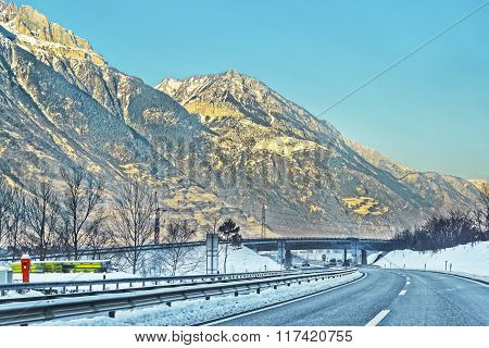 View Of Road With Electricity Transmission Lines In Switzerland In Winter