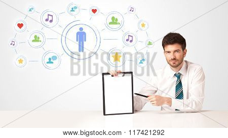 Businessman sitting at white table with social media connection background