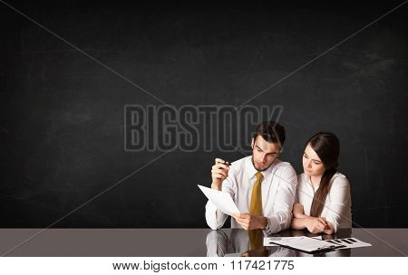 Business couple sitting at black table on black background