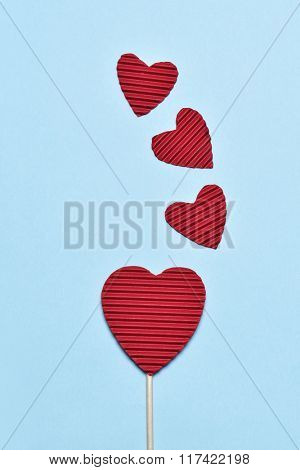 some hearts made with red corrugated paperboard, one of them stacked in a stick like a lollipop, against a blue background