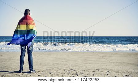a young caucasian man seen from behind wrapped in a rainbow flag looking at the ocean