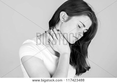 Woman With Neck Pain. Young Woman Holding Aching Neck Standing Black And White