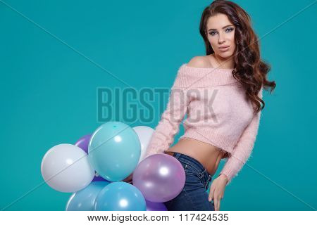 Young pretty woman with colored balloons, turquoise background