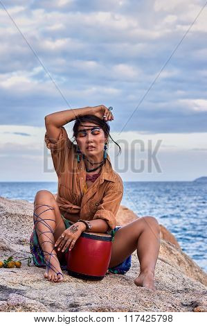 Woman shaman with drum, in mountain sea. Ethnic fashion photoshoot.