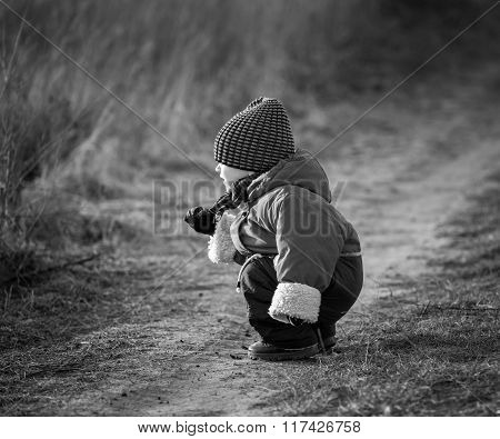 Young Happy Boy Playing Outdoor On Country Road. Black And White Photo