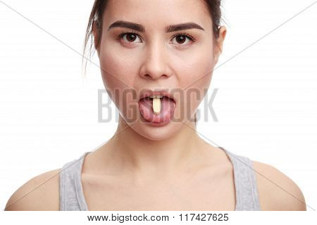Young woman taking a tablet. The girl's face close up with a pill on the tongue