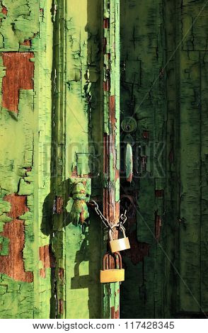 Old wooden door with green peeling paint and padlocks