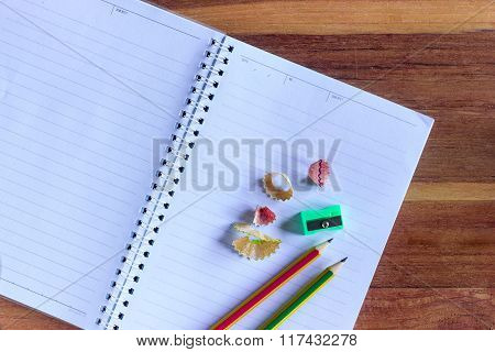 Two Sharpened Pencil, Pencil Sharpener And Unfolded Notebook On Wooden Office Desk