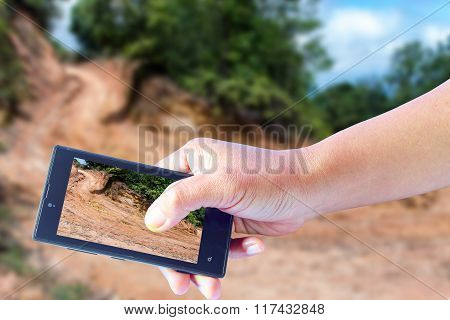 Business Conceptual- Focused On Right Hand Holding Mobile With Trekking Dirt Road Blurred Background