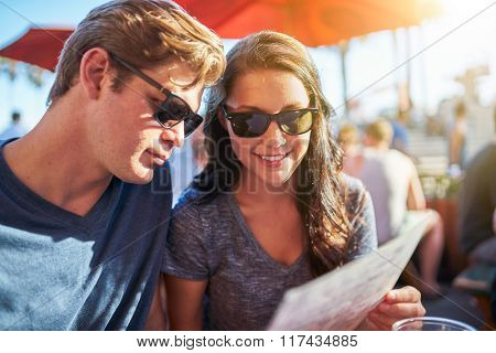 couple looking at menu seated in outdoor restaurant shot with selective focus and lens flare