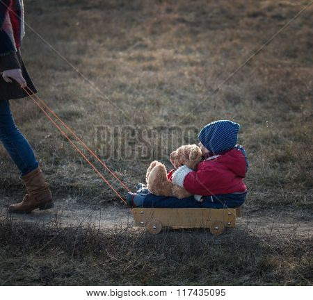 Young Happy Boy Playing Outdoor With His Teddy Bear And Trolley