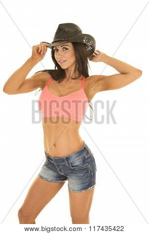 Cowgirl In Denim Shorts And Pink Sports Bra Both Hands On Hat