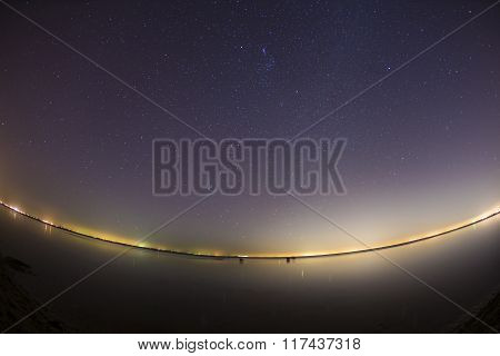 Starry night sky over clam water