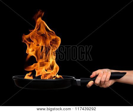 Woman's hand holding a frying pan with flames