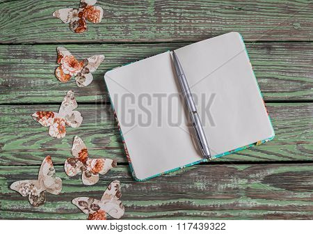 Open Clean Notepad And Homemade Paper Butterfly On A Wooden Vintage Background. Top View, Free Space