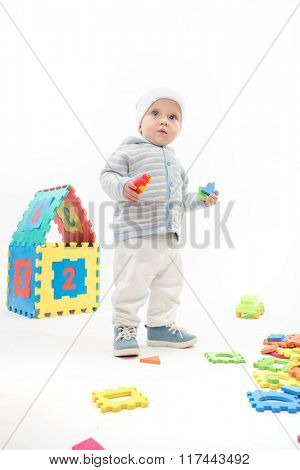 little child baby boy playing with puzzles isolated on white