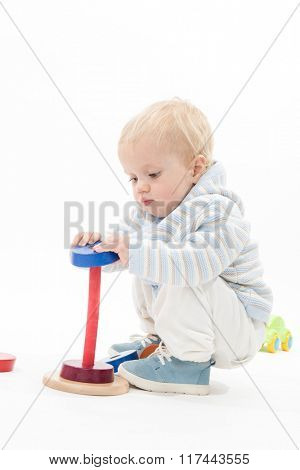 little child baby boy playing pyramid wooden toy isolated on white studio shot