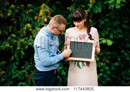 Expecting Pregnant Happy Couple Holding A Blank Charcoal Board.