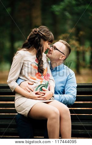 Beautiful Pregnant Stylish Couple Relaxing Outside In The Autumn Park Sitting On Bench.