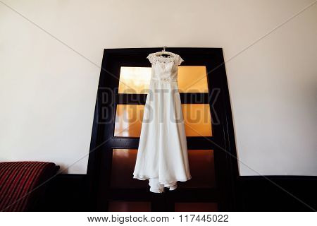 Beautiful Wedding Dress Hanging On A Door. Bridal Morning.