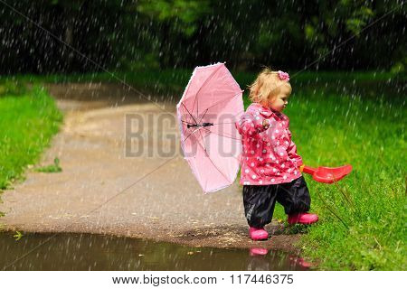 cute little girl with umbrella in raincoat and boots