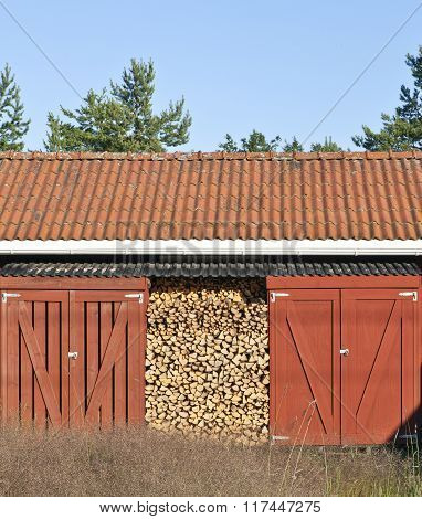 Firewood in a Falu Red Paint shelter.