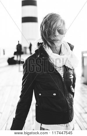 Black and white portrait photo of young woman posing outdoor in aviator style sunglasses, wind blowing