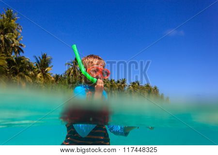 cute boy swimming and snorkeling in ocean