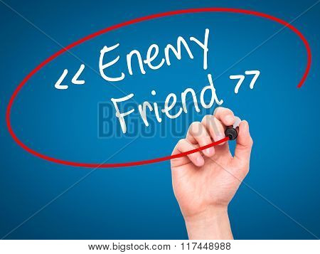 Man Hand Writing Enemy - Friend With Black Marker On Visual Screen.