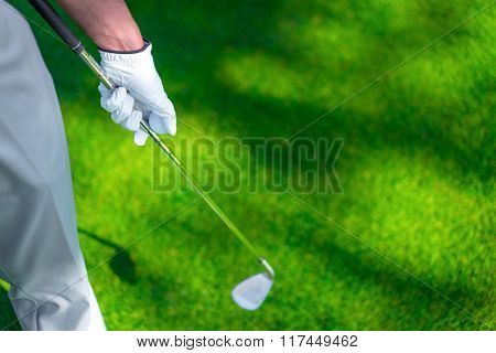 Man with a golf club on the lawn