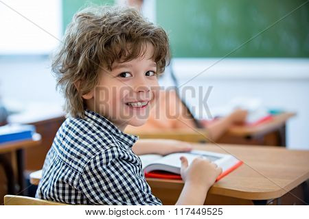 Little boy at a desk in classroom