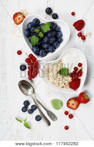 Healthy breakfast of muesli, berries with yogurt and seeds on white background -  Healthy food, Diet, Detox, Clean Eating or Vegetarian concept.