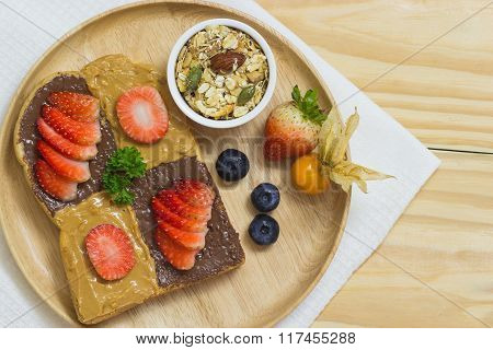 Selective Focus Of Bread Peanut Butter And Chocolate Spread On Wood Background With Strawberry And I