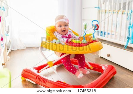 First steps of the girl in a baby walker