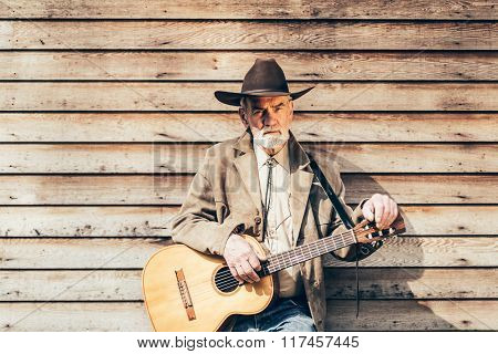 Middle Age Guitarist Leaning On Wooden House Wall