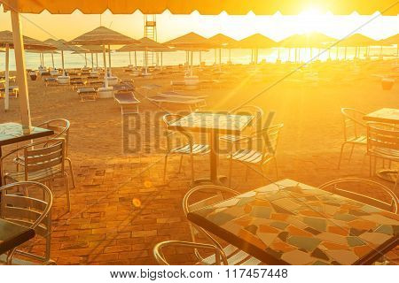 Beach with deck chairs, parasol, and bar during sunrise