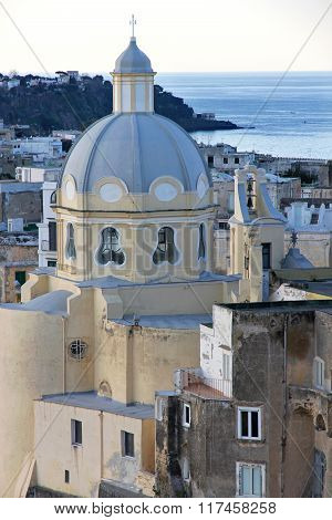 Italy. Gulf Of Naples. Procida Island. Church And Colorful Houses Of Corricella After The Sunset
