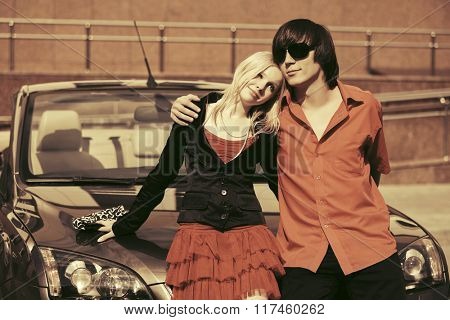 Happy young couple in love next to car