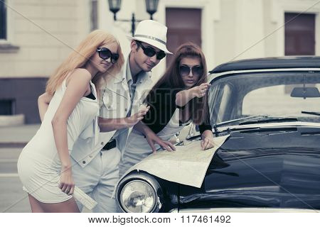 Young fashion people with a road map by retro car