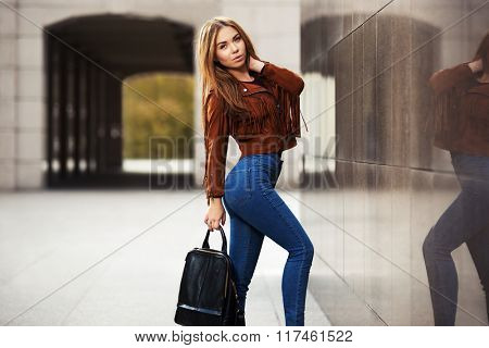 Young fashion woman in leather jacket with handbag walking on city street