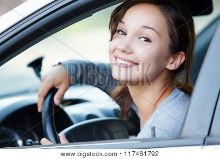 Pretty girl in a car smiling to you