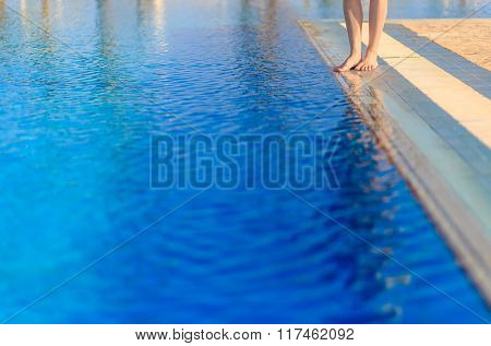 Young woman legs standing on border front of swimming pool