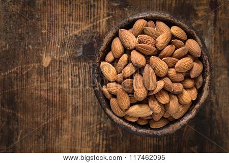 Almonds nuts in bowl on wooden background